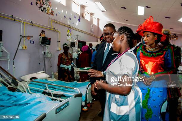 TOPSHOT An official of the Kamuzu Central Hospital briefs Malawi President Peter Mutharika and First Lady Gertrude Mutharika as they visit several...