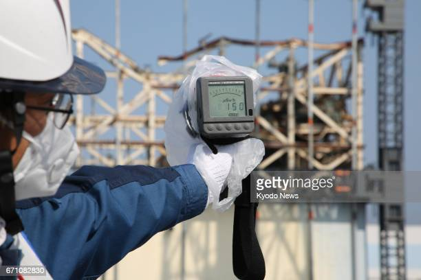 An official of Tokyo Electric Power Company Holdings Inc holds a Geiger counter 80 meters from the melted down No 1 reactor at the Fukushima Daiichi...