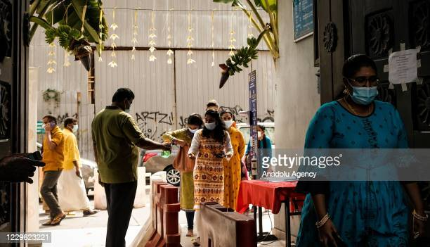 An official provides hand sanitizer at the entrance as Malaysian Hindus wears medical mask during commemorate the Deepavali celebration amid the...