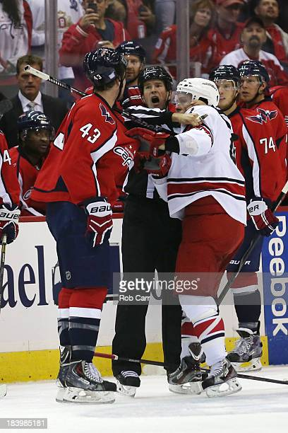 An official pulls apart Tom Wilson of the Washington Capitals and Brett Sutter of the Carolina Hurricanes during the first period at Verizon Center...