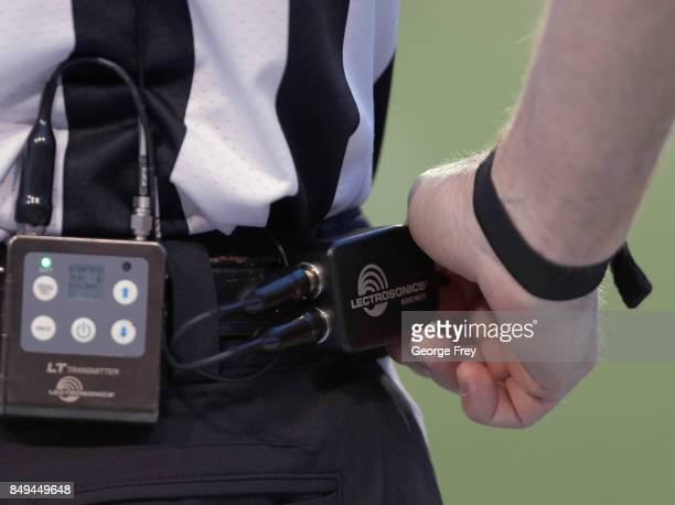 An official pushes the mic button on his communication gear during warmups before the start of an college football game against the against the Utah...
