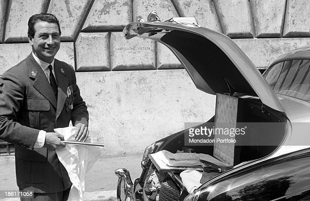 An official puts a banner inside a briefcase in the back of a car during the stay of the two royals Grace Kelly and Rainier III in Rome and their...