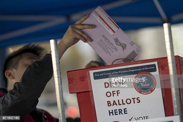 An official puts a mailin ballot into a box at the San Francisco City Hall polling location in San Francisco California US on Tuesday Nov 8 2016 The...