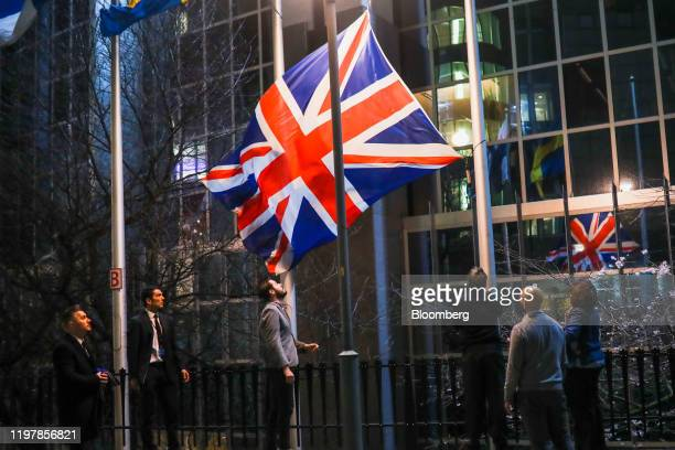 An official removes the British Union flag, also known as a Union Jack, from the European Parliament in Brussels, Belgium, on Friday, Jan. 31, 2020....