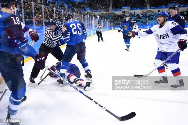 An official separates players in the men's playoffs qualifications ice hockey match between Finland and South Korea during the Pyeongchang 2018...