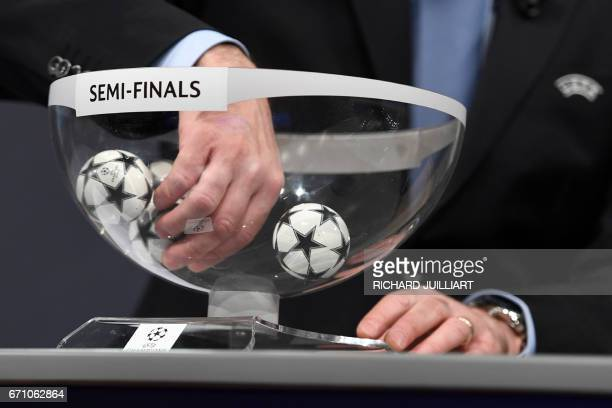 An official shuffles the balls ahead of the UEFA football Champion's league semifinals draw on April 21 2017 in Nyon / AFP PHOTO / Richard JUILLIART