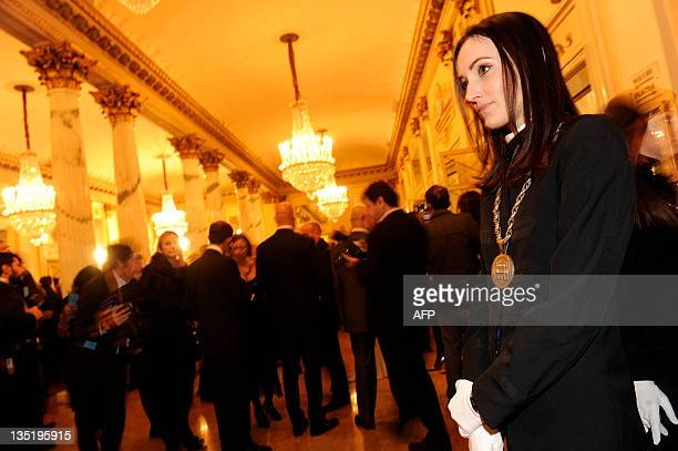 An official stands as spectators arrive to attend Don Giovanni opening the 20112012 season of La Scala opera house on December 7 2011 in Milan...