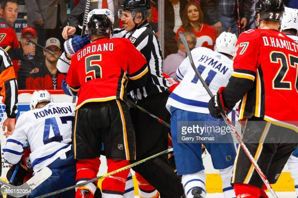 An official tries to separate Nikita Zaitsev of the Toronto Maple Leafs and Mark Giordano of the Calgary Flames in an NHL game against the Toronto...
