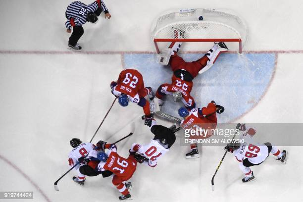 An official watches as playewrs scramble for the puck in the men's preliminary round ice hockey match between the Czech Republic and Switzerland...