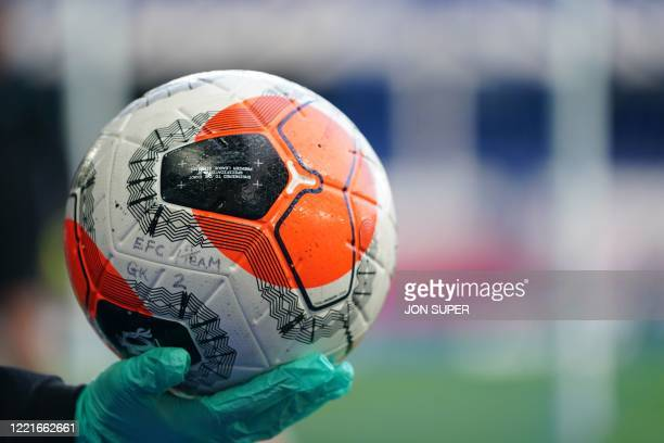 An official wearing a glove holds a match ball before kick off of the English Premier League football match between Everton and Liverpool at Goodison...