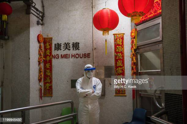 An official wearing protective gear stands guard outside an entrance to the Hong Mei House residential building at Cheung Hong Estate in the Tsing Yi...
