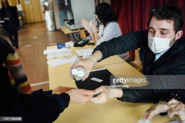 An official wears a face mask while offering hand sanitizer gel to a voter at a polling station during the first round of voting in the local mayoral...