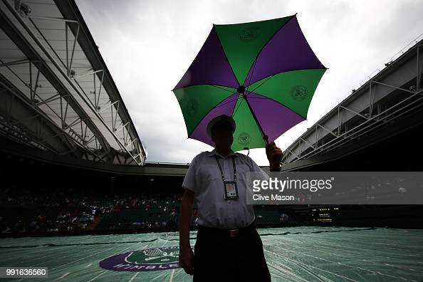 An official with an umbrella as rain stops play on day three of the Wimbledon Lawn Tennis Championships at All England Lawn Tennis and Croquet Club...