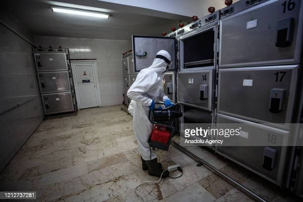 An official with protective suit disinfects a morgue after process of ghusl to the coronavirus victim at Zincirlikuyu Gasilhane, place where ghusl is...