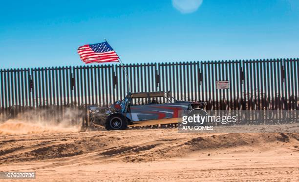 An offroad vehicle with a US flag drives near the USMexico border fence at the Imperial Sand Dunes Recreation Area east of Calexico California on...