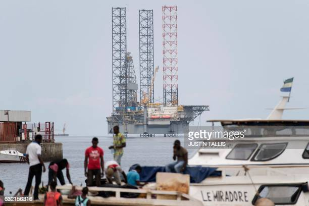 An offshore oil rig is pictured off the coast of PortGentil as people carry goods from a boat to the shore in Gabon on January 19 2017 / AFP / Justin...