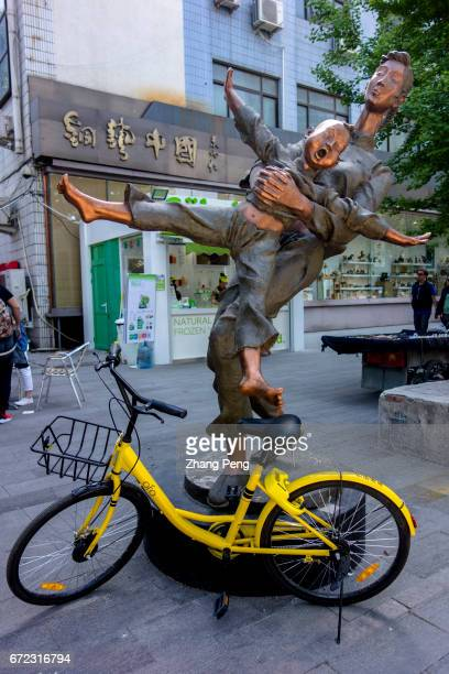 An OFO sharing bike is placed under a city statue With the popularity of sharing bikes destroy and misplacing of bikes become new problems for city...