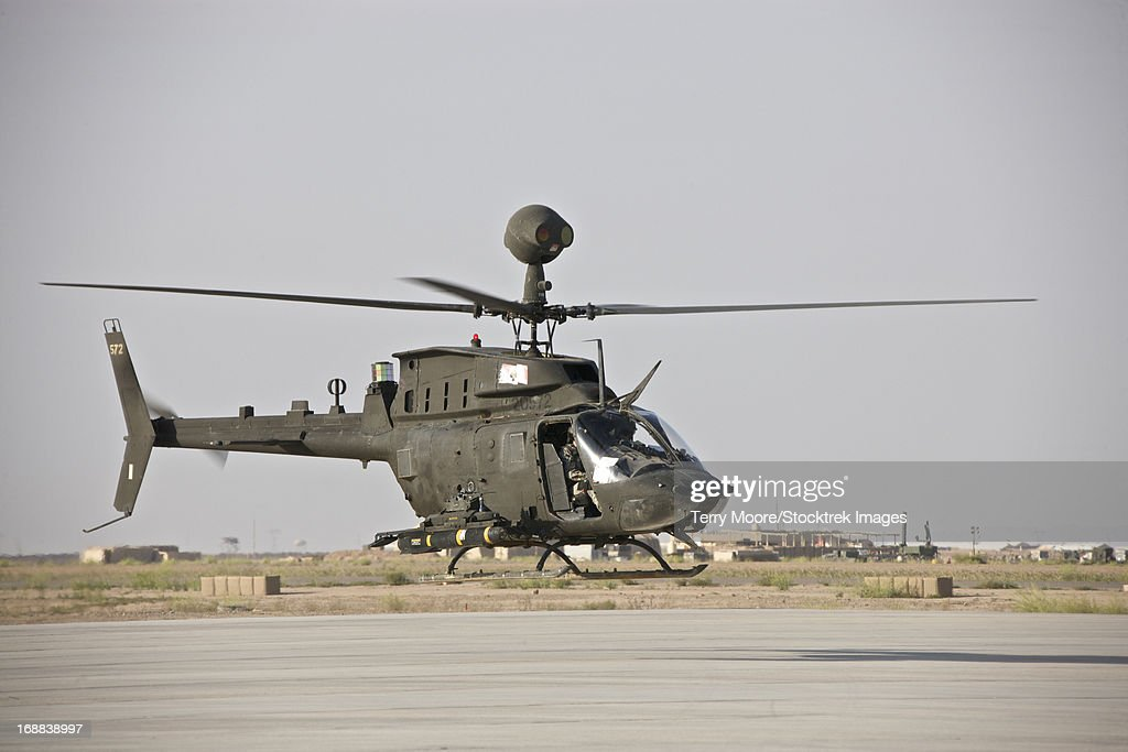 An OH-58D Kiowa helicopter takes off from COB Speicher, Tikrit, Iraq, during Operation Iraqi Freedom. : Stock Photo