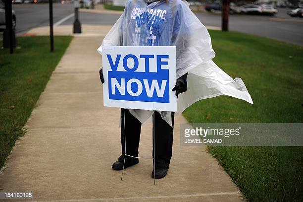 An Ohio Democratic Party volunteer displays a placard to encourage public for early voting in front of an early voting center in Columbus Ohio on...