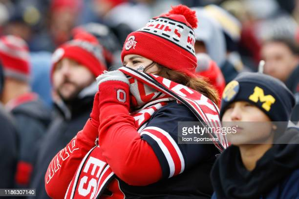 An Ohio State fan watches the action on the field while trying to stay warm during a regular season Big 10 Conference game between the Ohio State...