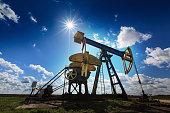 An oil and gas well against a sunny sky