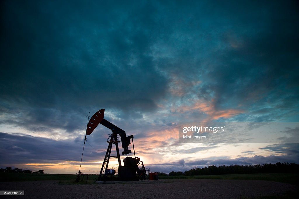 An oil derrick, a well head pump arm with frame, silhouetted against the evening sky. Oil business.  : Stock Photo