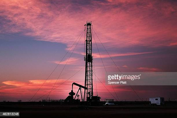 An oil drill is viewed near a construction site for homes and office buildings on February 5 2015 in Midland Texas As crude oil prices have fallen...