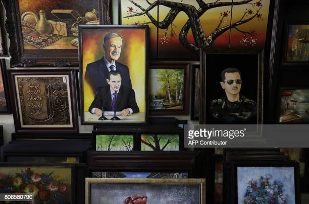 An oil painting depicting a portrait of Syrian President Bashar alAssad and his late father Hafez alAssad are seen at an art gallery in the capital...