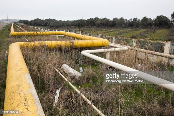 an oil pipeline runs beside a road - azerbaijan stock pictures, royalty-free photos & images