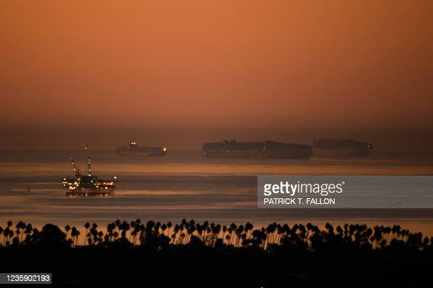 An oil platform stands offshore as cargo shipping container ships wait in the Pacific Ocean to enter the Port of Los Angeles and Port of Long Beach...