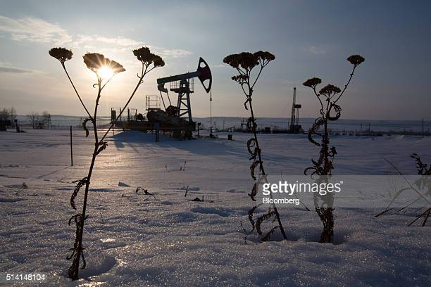 An oil pumping jack also known as a 'nodding donkey' operates in a snow covered oilfield near a derrick right during drilling operations in an...
