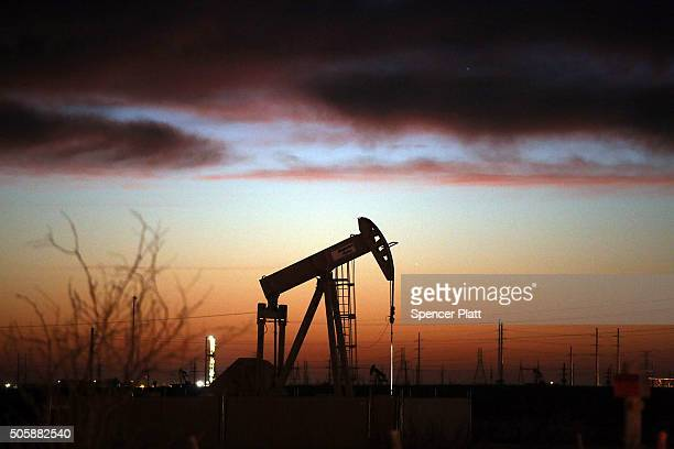 An oil pumpjack works at dawn in the Permian Basin oil field on January 20 2016 in the oil town of Andrews Texas Despite recent drops in the price of...