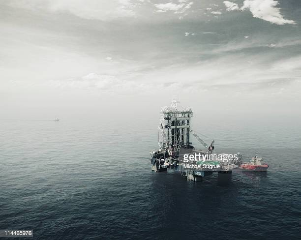 An oil rig in the middle of a body of water.