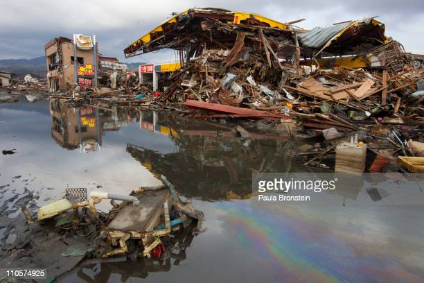 An oil slick is seen in the water surrounded by destruction on March 22 2011 in Kesennuma Miyagi Japan Eleven days after the magnitude 9 earthquake...