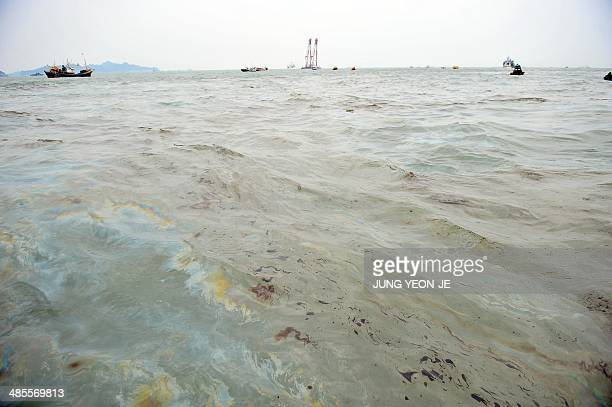 An oil spill is seen at the site of a capsized ferry at sea off Jindo on April 19 2014 Investigators on April 19 arrested the captain accused of...
