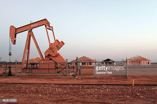 An oil well is viewed near a construction site for homes on February 5 2015 in Midland Texas As crude oil prices have fallen nearly 60 percent...