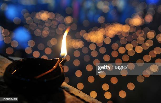 An oil wick lamp sits on a wall at a temple for the Hindu God Shiva during the Karthigai Deepam a festival where devotees light oil wick lamps at the...