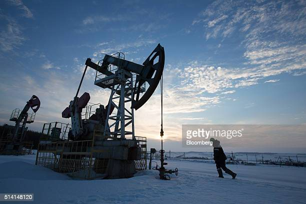 An oil worker inspects a pumping jack also known as a 'nodding donkey' during drilling operations in an oilfield operated by Bashneft PAO in the...