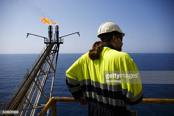 An oil worker looks on as flames burn from a gas venting pipe on the Casablanca oil platform operated by Repsol SA in the Mediterranean Sea off the...
