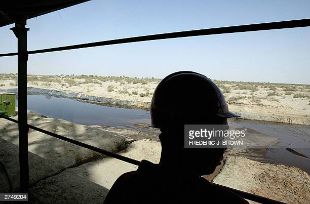An oil worker on site at an oil refinery in Lunnan 13 September 2003 on the edge of the Taklimakan Desert in western China's Xinjiang province An...