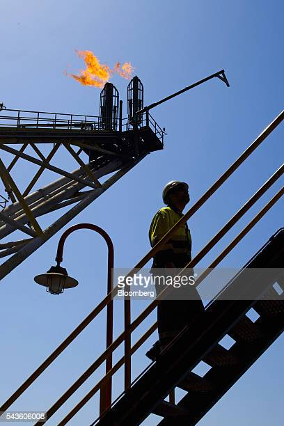 An oil worker passes the waste gas venting pipes on the Casablanca oil platform operated by Repsol SA in the Mediterranean Sea off the coast of...