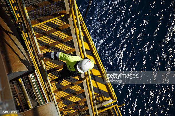 An oil worker stands high above the waterline on an access stairs on the Casablanca oil platform operated by Repsol SA in the Mediterranean Sea off...