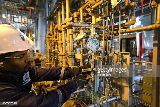 An oil worker uses a metal wrench to check pipework aboard the Agbami floating production storage and offloading vessel operated by Chevron Corp in...