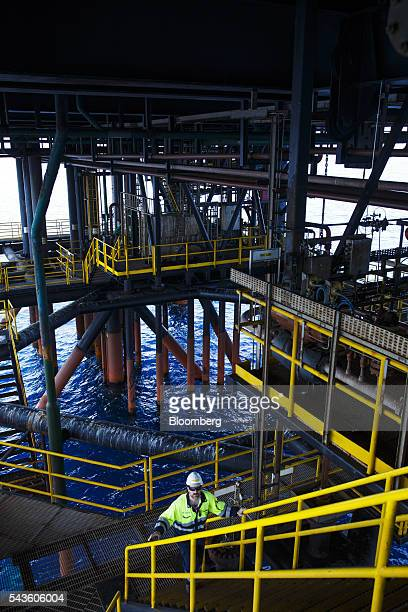 An oil worker walks along an access way on the lower structure of the Casablanca oil platform operated by Repsol SA in the Mediterranean Sea off the...