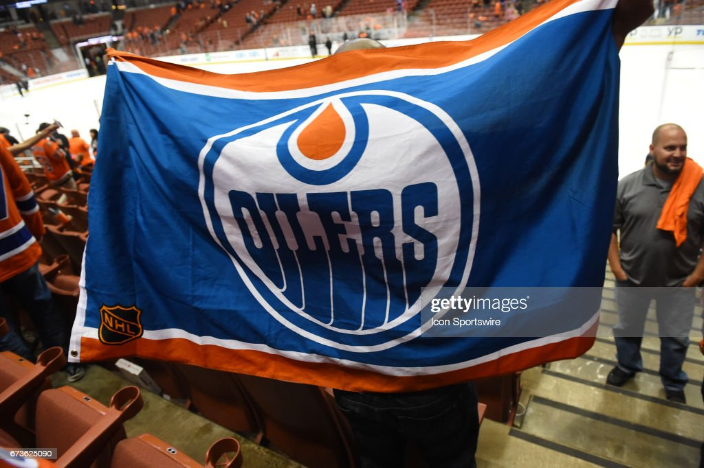 new style 97832 c5391 An Oilers fan celebrates the victory by unfolding an Oilers ...