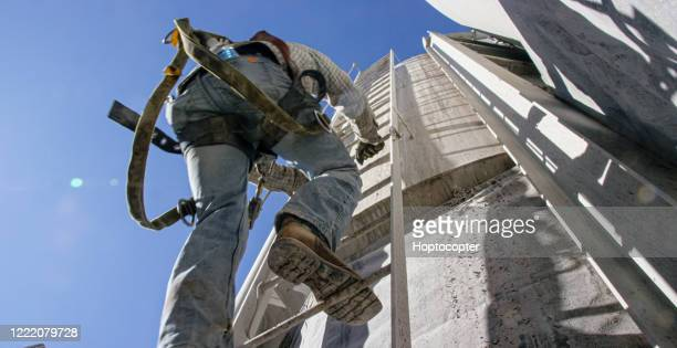 an oilfield worker climbs a ladder on the side of a mud tank at an oil and gas drilling pad site on a sunny morning - boot stock pictures, royalty-free photos & images