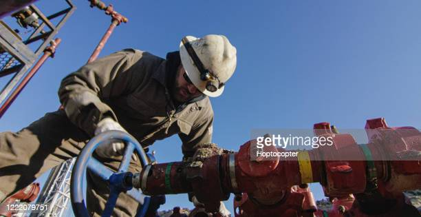 an oilfield worker in his thirties pumps down lines at an oil and gas drilling pad site on a cold, sunny, winter morning - gasoline stock pictures, royalty-free photos & images