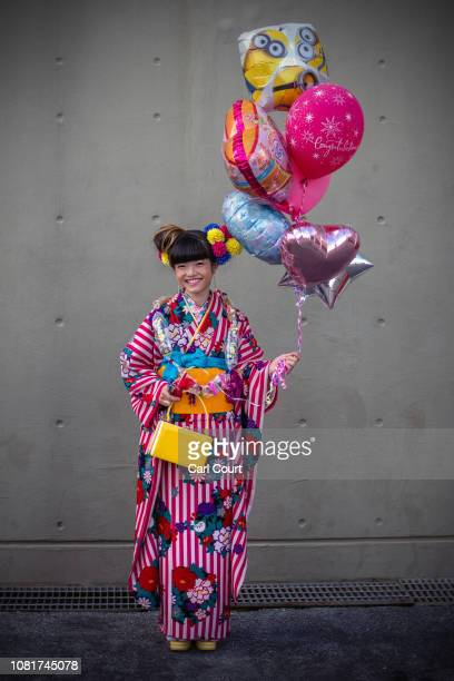 An Okinawan woman in a kimono holds balloons as she poses for a photograph after attending a ceremony on Coming of Age Day on January 13, 2019 in...