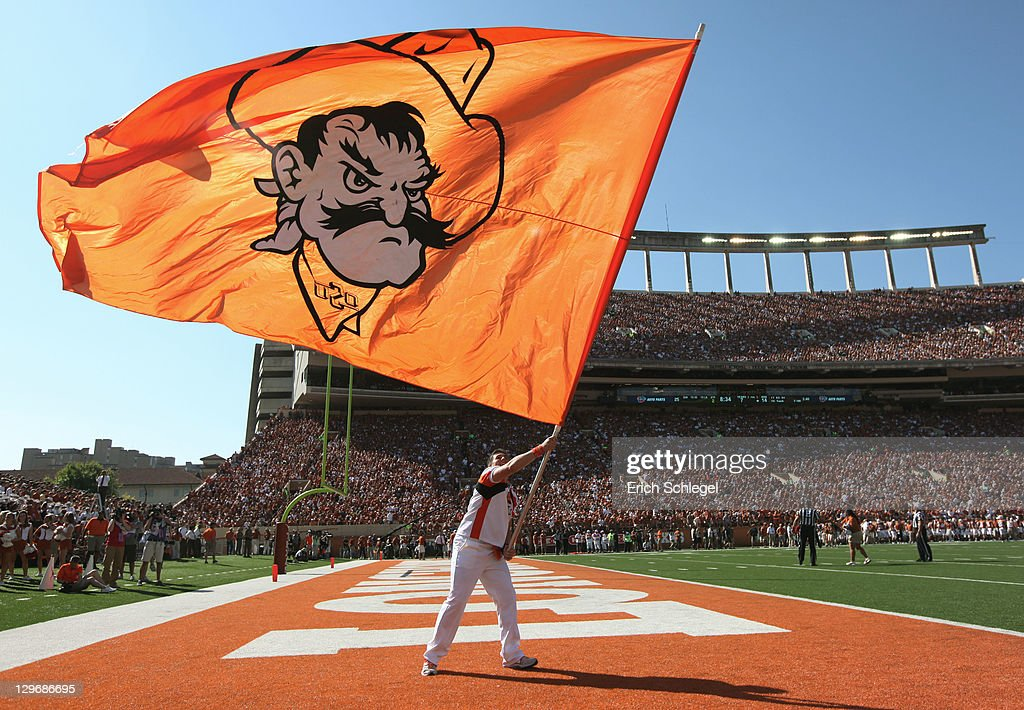 An Oklahoma State cheerleader flies the Cowboys' flag after