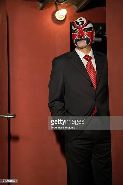 an old actor wearing traditional chinese face paint and a business suit poses in a doorway. - peking opera stock photos and pictures